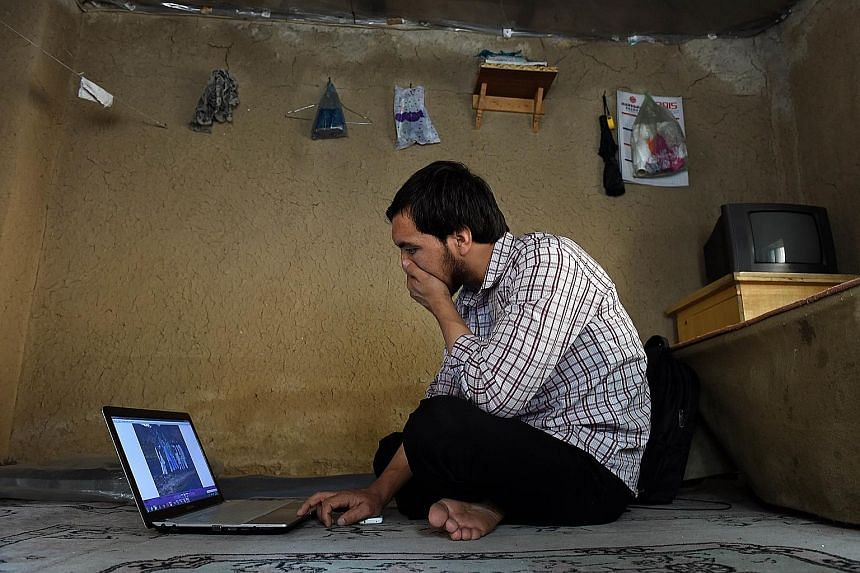 Mr Abdullah Karim Aminy looking at a photograph of his cousin on a laptop in Kabul. His cousin is one of a growing number of young Afghans who have left home to fight in Syria. Mr Abdullah's cousin has been killed in battle.
