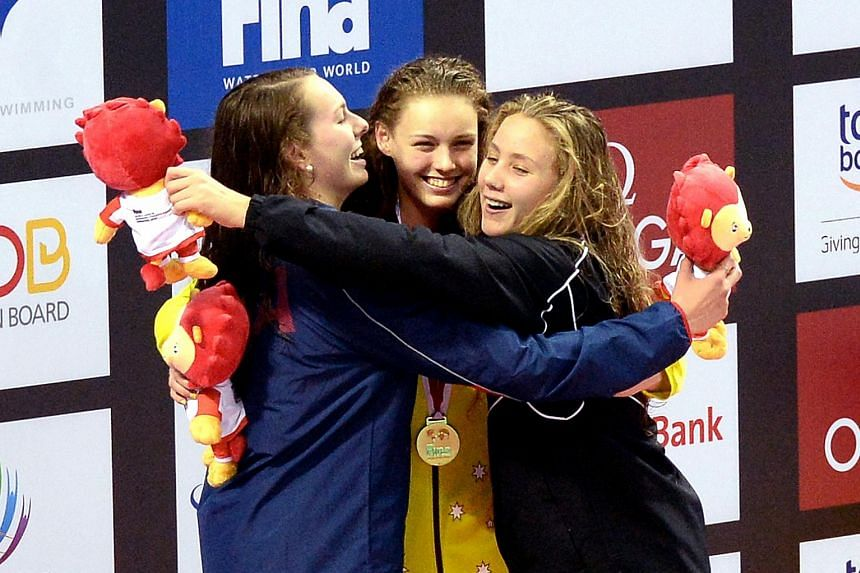Minna Atherton (centre) being congratulated by the other two medallists after she won the 100m backstroke last night. The Brisbane teenager achieved the feat in a world junior record 59.58sec.