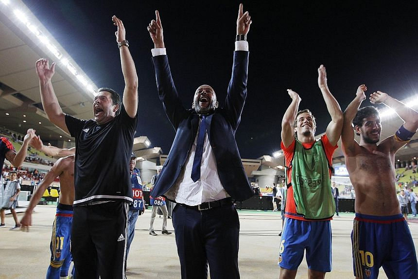 Coach Nuno Espirito Santo (centre) and captain Dani Parejo (right) acknowledging the cheers of supporters after Velencia edged out Monaco and qualified for the Champions League's knockout stage on Tuesday. The Spanish club are back among Europe's eli