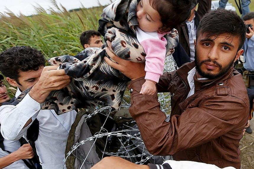 A child being handed across a barbed wire fence as Syrian migrants try to enter Hungary from areas near the country's border with Serbia.