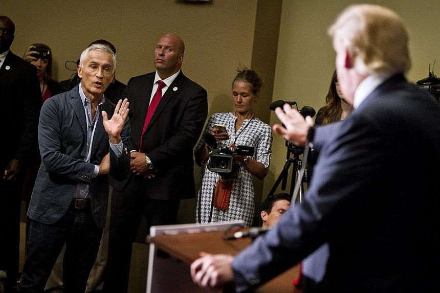 Republican presidential hopeful Donald Trump (right) sparring with Univision reporter Jorge Ramos during a Tuesday press conference.