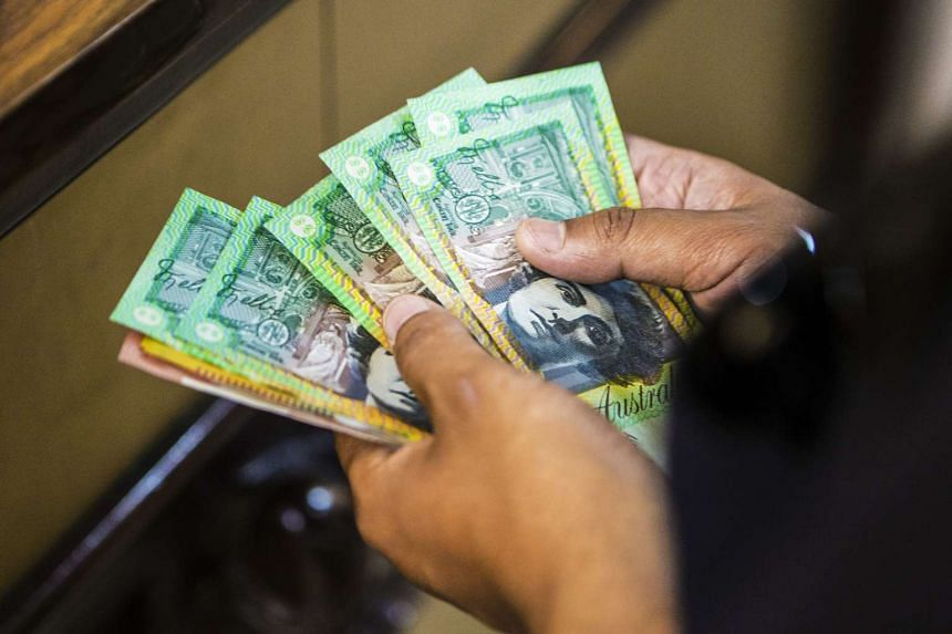 A file picture of a customer counting the Australian dollar. PHOTO: BLOOMBERG
