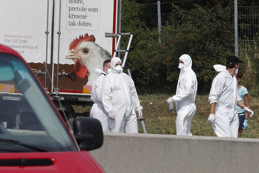Forensic officers work near a truck which was found to contain a large number of dead migrants on a motorway near Neusiedl am See, Austria, on Aug 27, 2015.