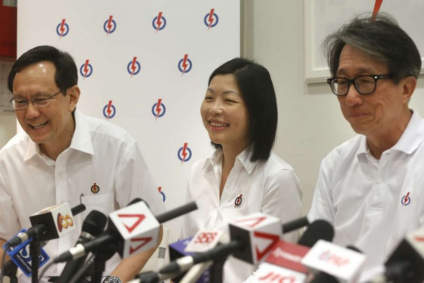 Ms Cheryl Chan (centre) with retiring MP Raymond Lim (left) and Manpower Minister Lim Swee Say at the press conference confirming her as the PAP candidate for Fengshan SMC.
