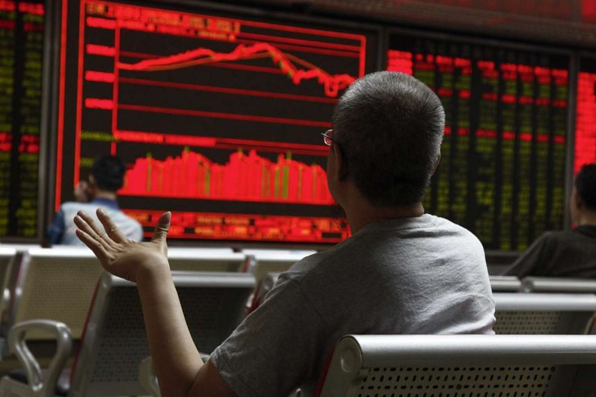 An investor reacts while monitoring stock data on an electronic board at a securities brokerage house in Beijing, China on Aug 26, 2015.
