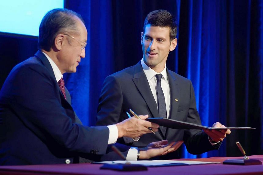 Djokovic (right) and World Bank Group president Jim Young exchange a memorandum during a Unicef press conference.