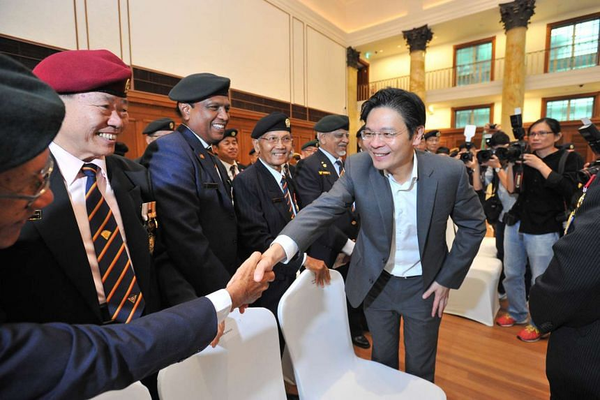 Minister for Culture, Community and Youth Lawrence Wong (right) interacting with members of the SAF Veterans League, inside the City Hall Chamber, (now part of the National Gallery Singapore) on Aug 27, 2015.