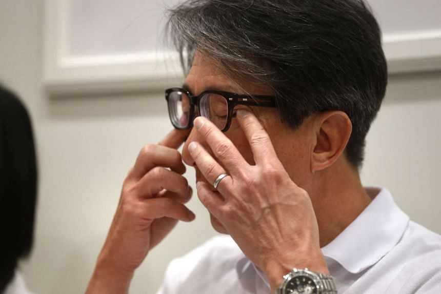 Manpower Minister Lim Swee Say wiping away tears after paying tribute to retiring MP Raymond Lim.