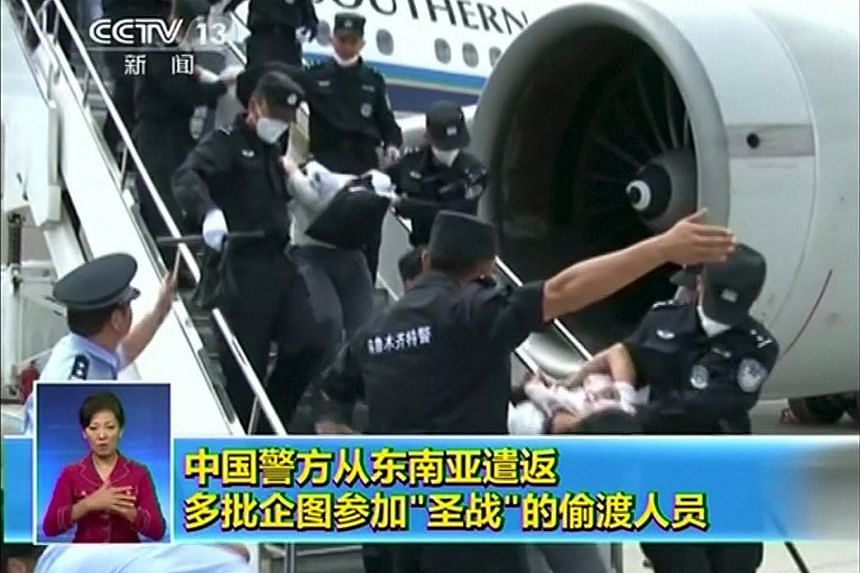 People getting deported from Thailand, believed to be Xinjiang natives attempting to go to Turkey to join militant outfits, are seen being brought off an airplane by police at an unidentified location in China on July 9, 2015.