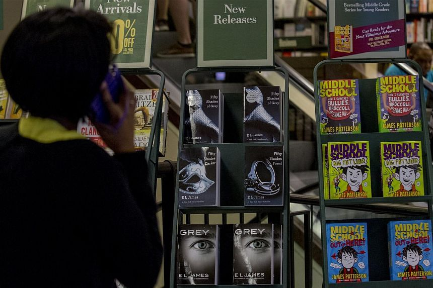 A woman looks at books from the Fifty Shades Of Grey series in a bookstore in New York on June 18, 2015.