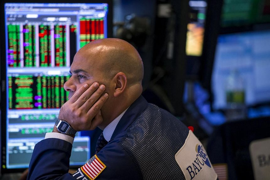 A trader looking at stock prices on a screen while working on the floor of the New York Stock Exchange on Aug 26, 2015.