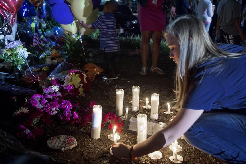People take part in a candlelight vigil on the front driveway of WDBJ-TV's television studios on Aug 27, 2015, in Roanoke, Virginia.