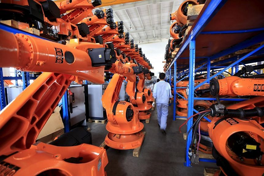 A worker walks past second-hand robots used to make Audi A3s in a factory in Shanghai, on Aug 21, 2015.
