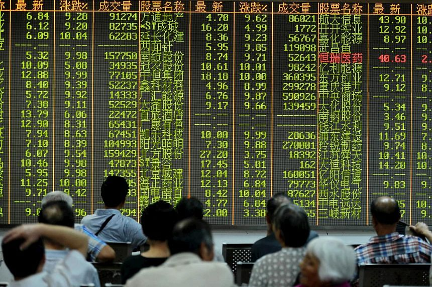 Investors look at stock information on an electronic board at a brokerage house in Hangzhou, Zhejiang province.