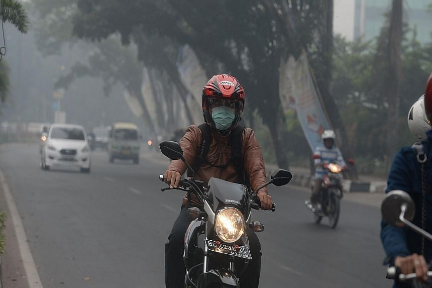 The acrid smell of burnt peat hangs heavily in the air as drivers and motorcyclists navigate the roads under challenging conditions. In South Sumatra, masks have been distributed to residents while schools have closed in Riau province.