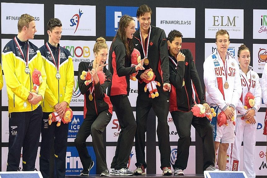 Canada's (in black and red) winning 4x100m freestyle mixed team of (from left) Penny Oleksiak, Taylor Ruck, Markus Thormeyer and Javier Acevedo celebrating their golden harvest.