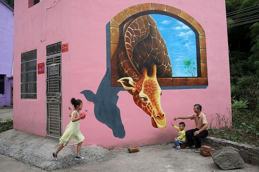 Tourists playing in front of a 3D painting on the wall of a house in Luoyuan village, in China's Zhejiang province, on Wednesday. The village hired a team to paint the pictures to attract tourists and improve the income of villagers, according to med
