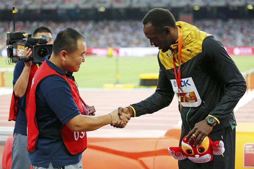 Usain Bolt shakes hands with Song Tao, the CCTV cameraman who knocked him down with a Segway.