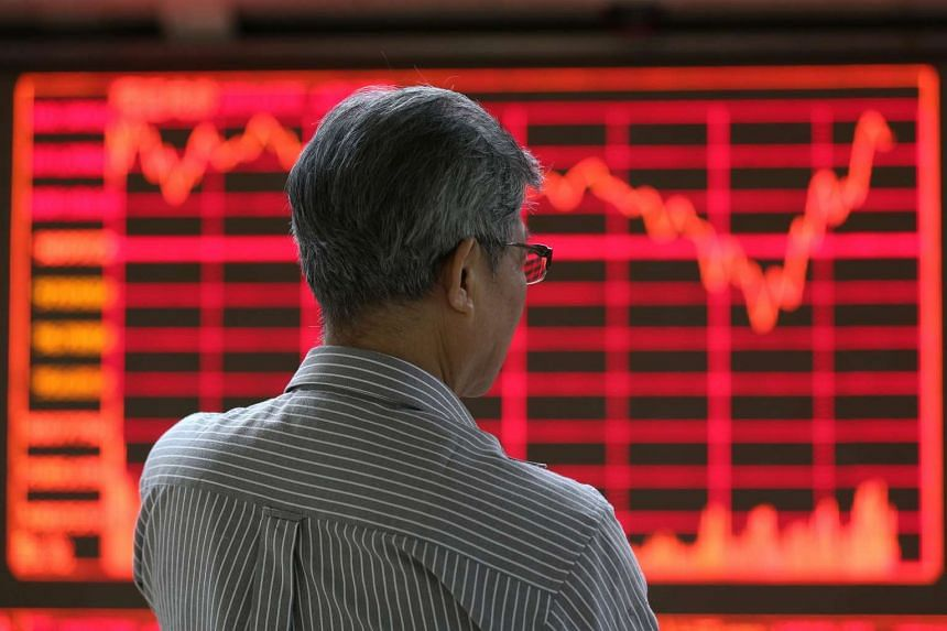 A stock investor stands in front of an electronic screen showing the stock composite index at a brokerage house in Beijing.