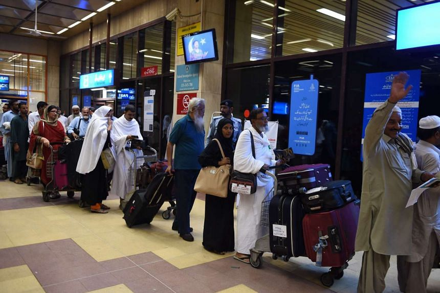 Pakistani pilgrims queue to check-in at an airport terminal for the first haj flight to Saudi Arabia, in Karachi on Aug 15, 2015.