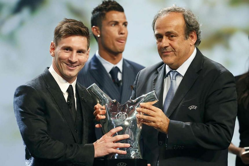 Lionel Messi (left) receives the Best Player award from UEFA president Michel Platini.
