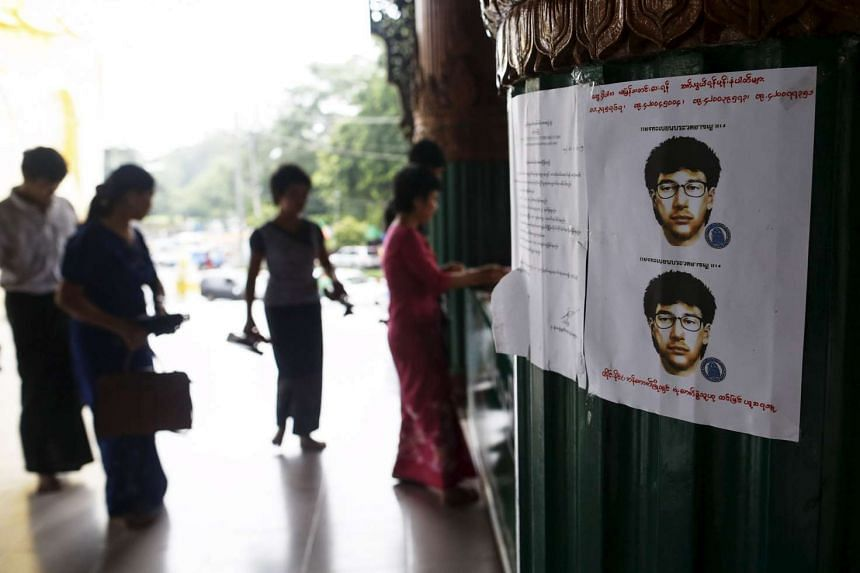 People gathering near a wanted poster for the main suspect of the deadly bomb blast.