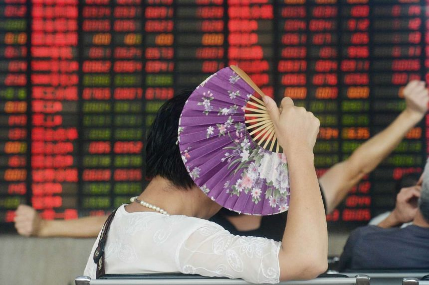 An investor holds a fan as she monitors share prices at a securities firm in Shanghai on Aug 26, 2015.