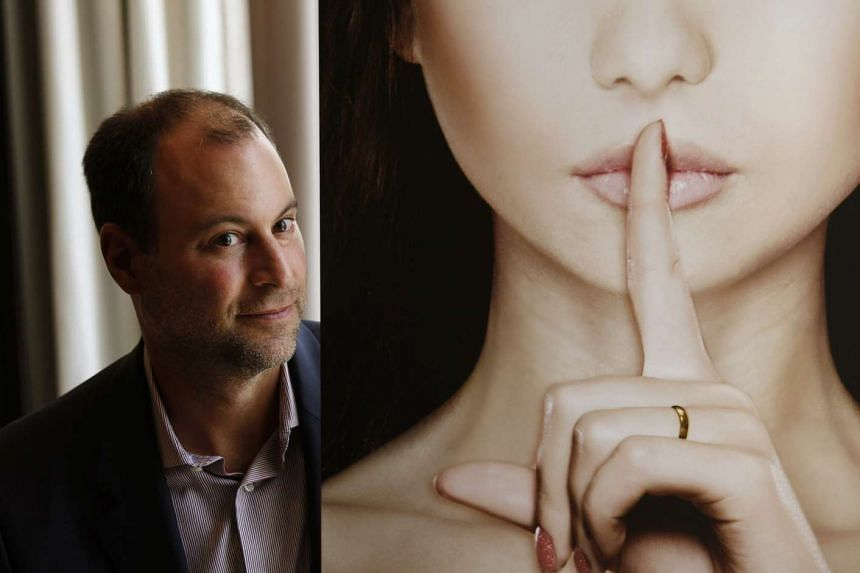 Ashley Madison founder Noel Biderman poses with a poster during an interview at a hotel in Hong Kong in this Aug 28, 2013, file photo.