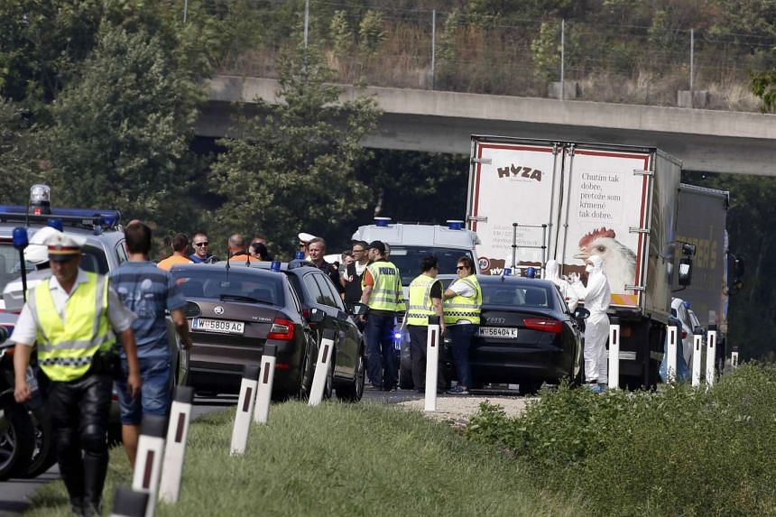 Forensic investigators work on a refrigerated truck in which the bodies of between 20 and 50 migrants were found.