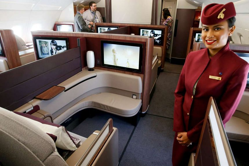 A Qatar Airways crew member presents the first-class seats of an Airbus A380 aircraft at the Paris Air Show.