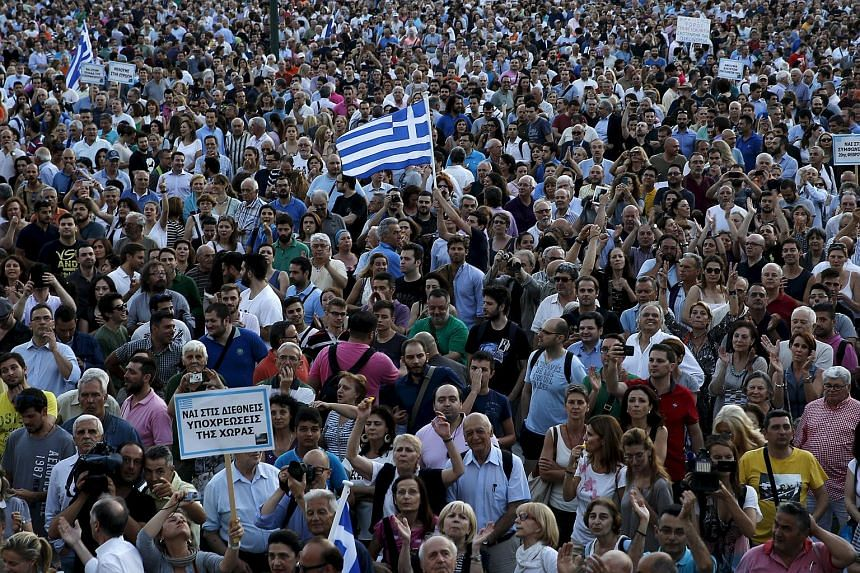 A man waves a Greek national flag as people rally outside parliament in this June 18, 2015 file photo.