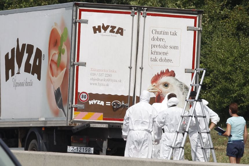 Forensic officers behind a truck, where at least 20 dead migrants were found, near Neusiedl am See, Austria, yesterday.