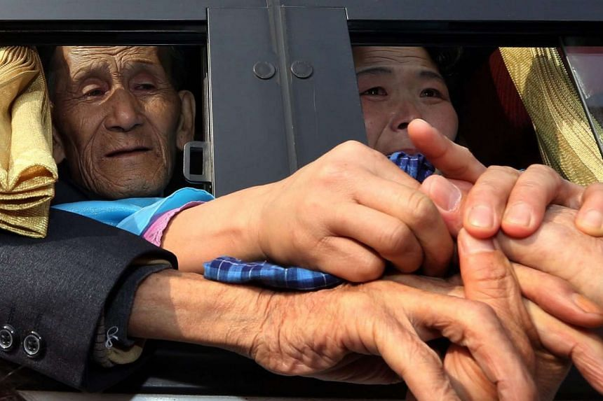 Separated families living in South Korea try to touch the hands of their North Korean relatives inside a bus after a brief reunion in this Feb 25, 2014 file photo.