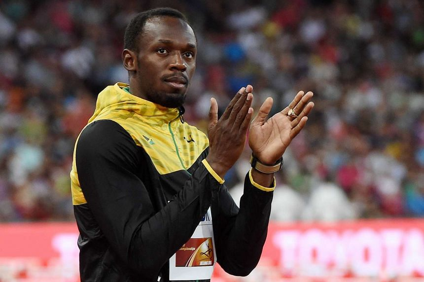 Usain Bolt applauds during the victory ceremony for the men's 200 metres athletics event on Aug 28, 2015.