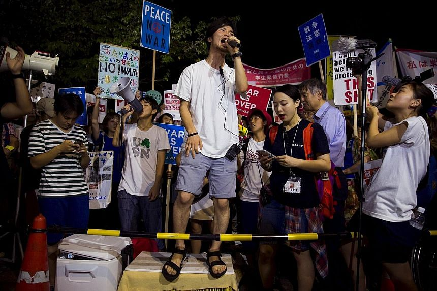 Mr Aki Okuda (with microphone), founding member of the protest group Students Emergency Action for Liberal Democracy, leading a protest outside Parliament in Tokyo last week. Japan has not seen significant student protests since the 1960s and the gro