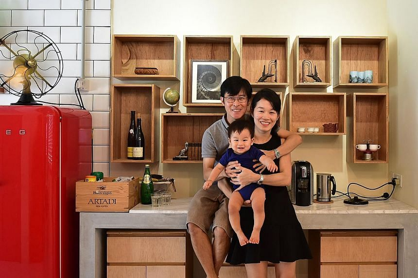 Doing their part to preserve bits of the past, Mr Chue Guan Lin and Ms Leem Pei Shan, with their son, Zhi Ler (all above), recycled wooden crates, used as storage containers in the kitchen (above), and made the front door the toilet door (left). Art