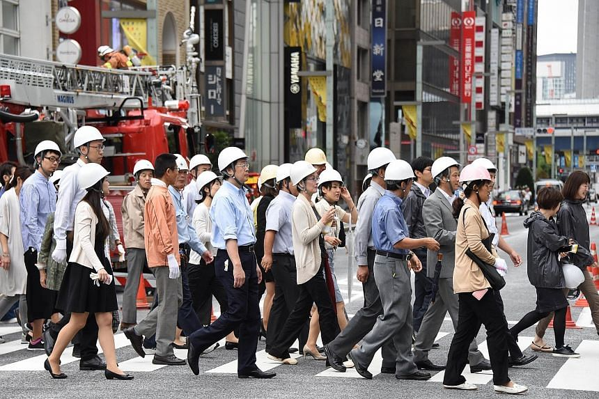 Participants making their way to a shelter during an annual disaster drill in the Ginza shopping and business district in Tokyo yesterday. Some 5,000 people working and living in the Chuo district took part in the exercise, which trains people on wha