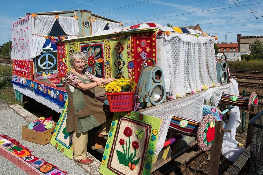 """German peace activist Christa Senberg posing with an old diesel locomotive covered with knitted works in Zossen, Germany. The movement, """"Knitting for Peace"""", which was co-initiated by Ms Senberg, is being held for the second time after its success in"""