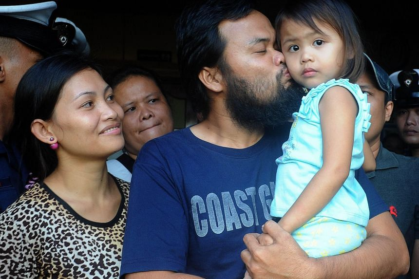 Philippine Coast Guard officer Rod Pagaling, one of the two hostages who escaped after elite military forces launched a risky rescue effort last week, with his wife and daughter.