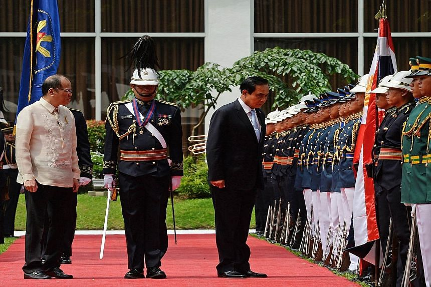 Mr Prayut Chan-o-cha reviewing the guard of honour during a welcoming ceremony in the Malacanang Palace grounds in Manila yesterday as Philippine President Benigno Aquino looked on.