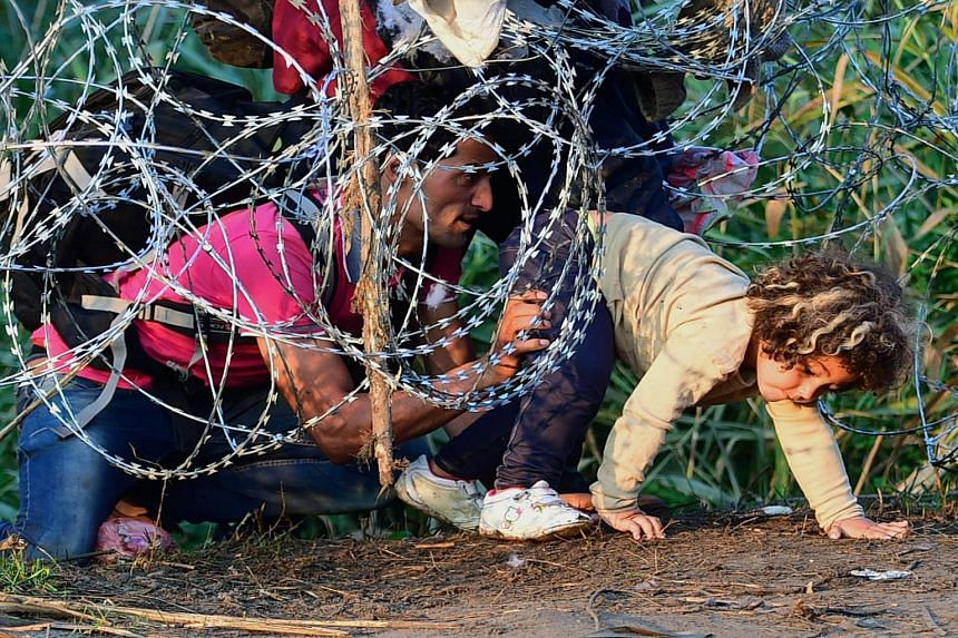 "A migrant family creep under a barbed fence at the Hungarian-Serbian border. Some experts believe the term ""migrant"" is no longer a fitting word to use to describe the horror unfolding in the Mediterranean."