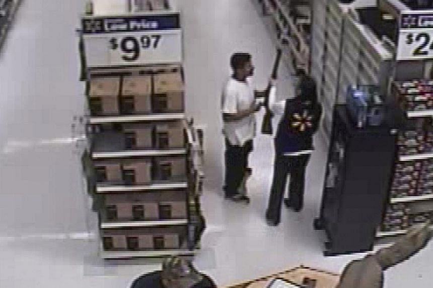 A video grab from a Walmart store shows Mario Valencia holding a rifle as an employee reaches for it in the Walmart store in Arizona on Feb 19. He would later go on to be charged with robbing a convenience store, breaking into a church, invading a ho