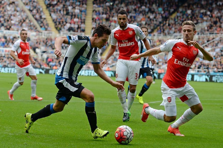Newcastle's Florian Thauvin (left) vies with Arsenal's Nacho Monreal (right).