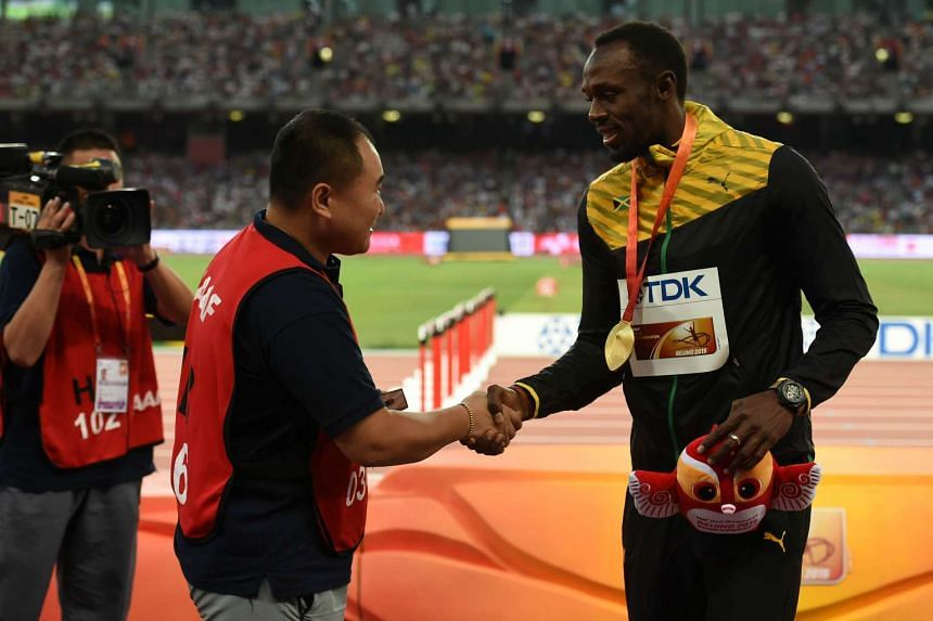 Chinese broadcast journalist Tao Song (left) shaking hands with Jamaica's gold medallist Usain Bolt (right). Tao interupted Bolt's celebrations after winning the 200m final when he crashed into him whilst filming from a segway motorised scooter besid