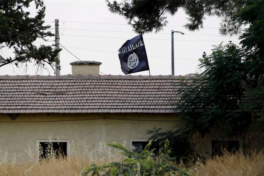 An ISIS flag flies over the custom office of Syria's Jarablus border gate.