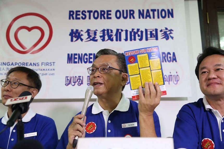 Singaporeans First Secretary-General Tan Jee Say (centre) holding up the party campaign manifesto.