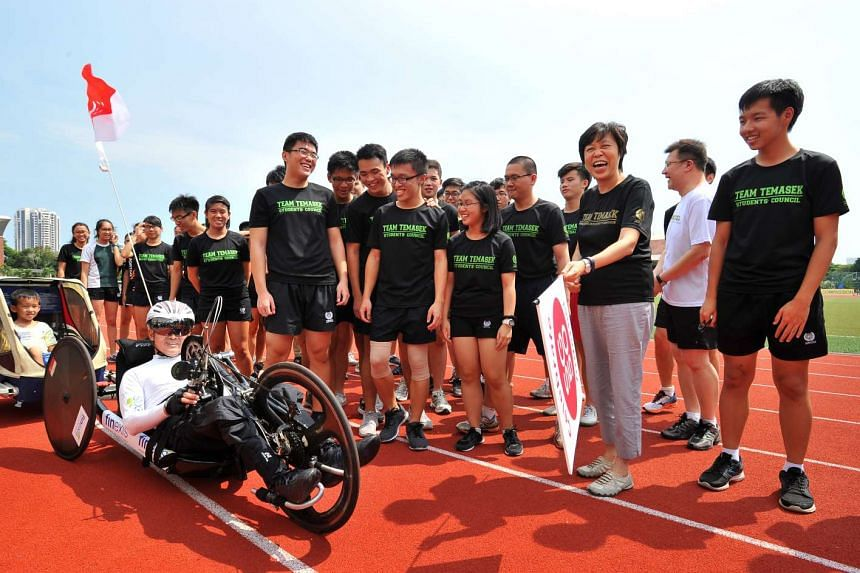 Dr William Tan in his handcycle, with pre-schooler Ethan Teng, five, in the child chariot. With them are TJC students who are acting as pacers, and TJC principal Susan Leong (holding flag).