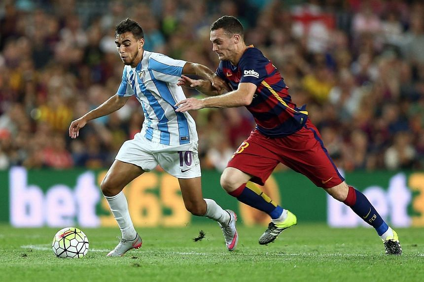 FC Barcelona's Belgian defender Thomas Vermaelen (right) fights for the ball with Malaga CF's Portuguese Ricardo Horta, during their Spanish Primera Division soccer match at the Camp Nou stadium in Barcelona, northeastern Spain, on Aug 29, 2015.