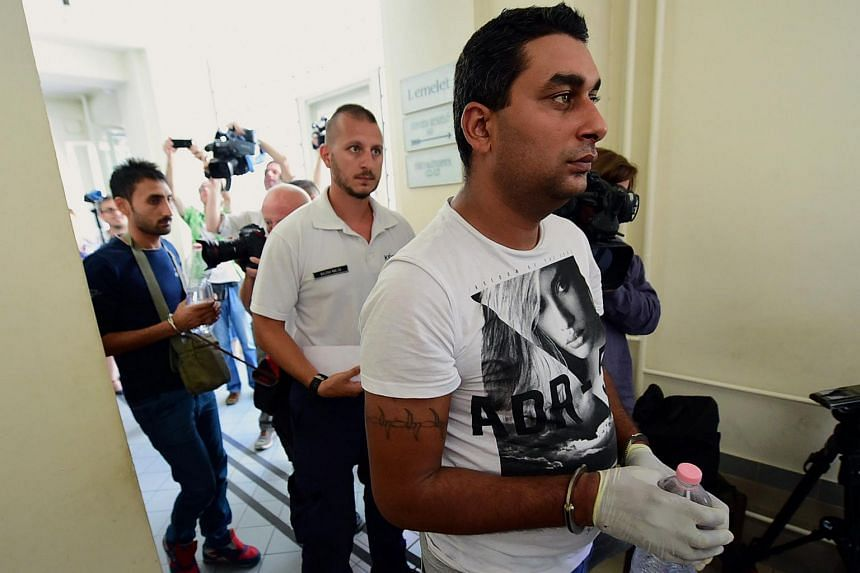 Two (right) and (left) of four suspects are led by a Hungarian police official (centre) into the Kecskemet courtroom on Aug 29, 2015.