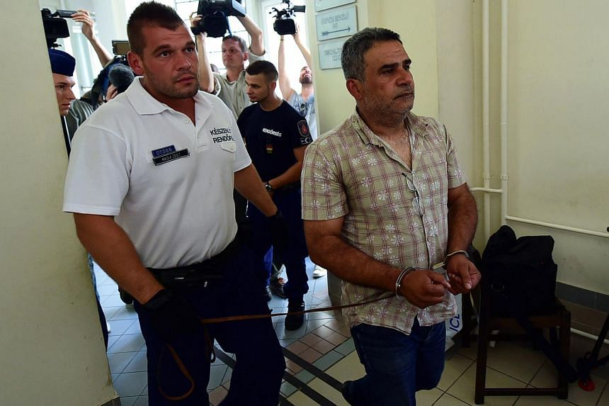 One (right) of four suspects is led by a Hungarian police official (left) into the Kecskemet courtroom on Aug 29, 2015.